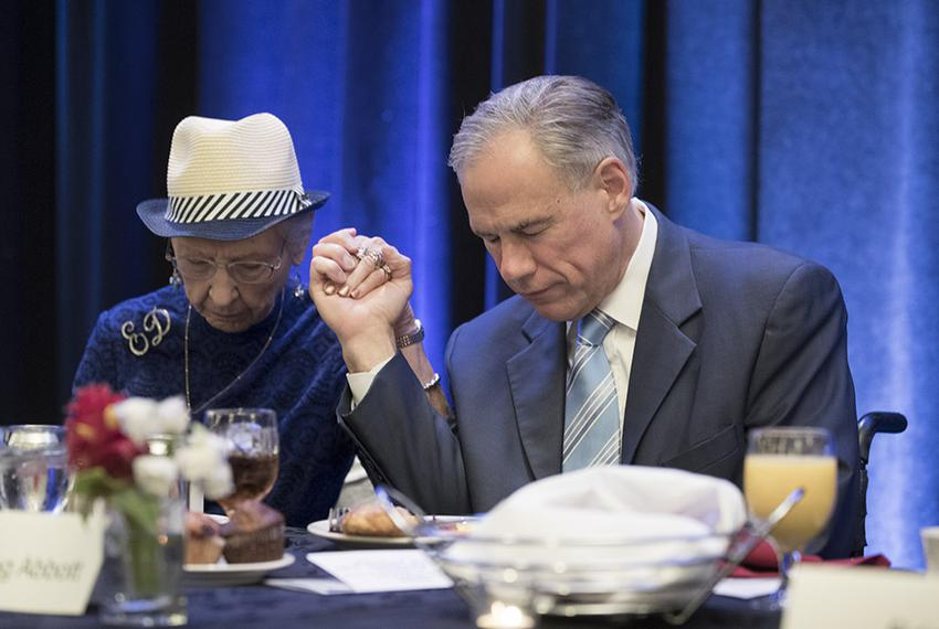 Gov. Greg Abbott prays with event organizer Evelyn Davison at the 66th annual Texas State Prayer Breakfast in Austin on Ma...