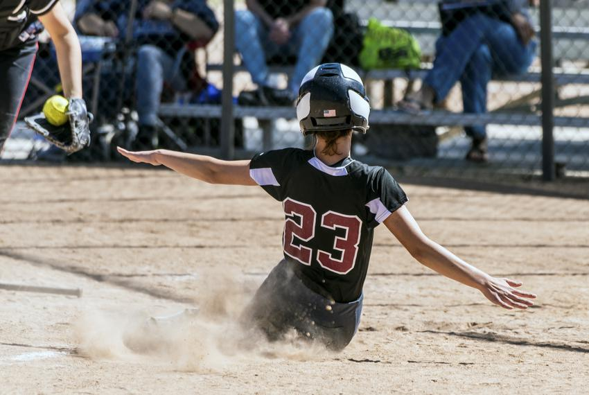 A teenage softball player in black uniform slides into home plate.