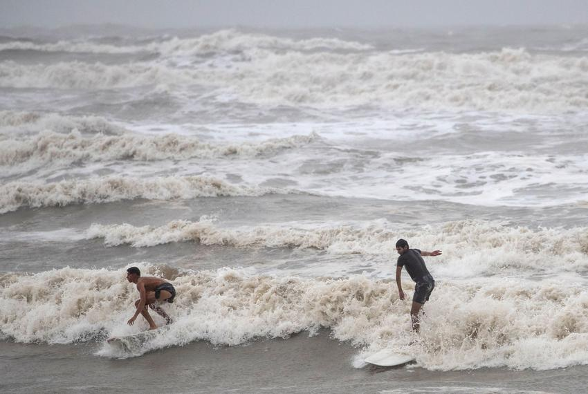 Surfers rode high swells from Hurricane Hanna in Galveston in July. The city is currently under mandatory evacuation in anti…