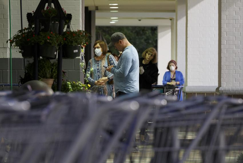 People with and without masks wait outside of a grocery store in Houston on March 31, 2020.