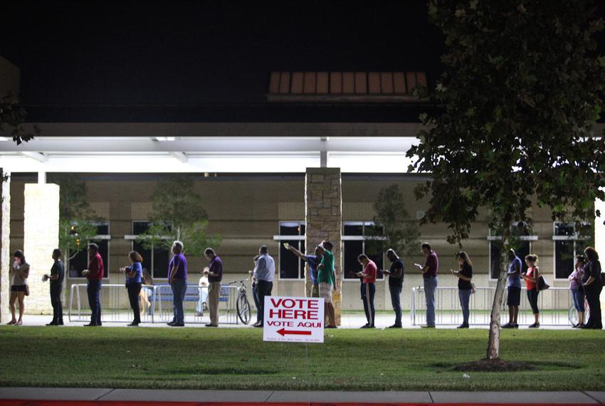 People wait to vote after polling places' official 7:00 closing time, at Tompkins High School in Katy in Fort Bend Co. on No…