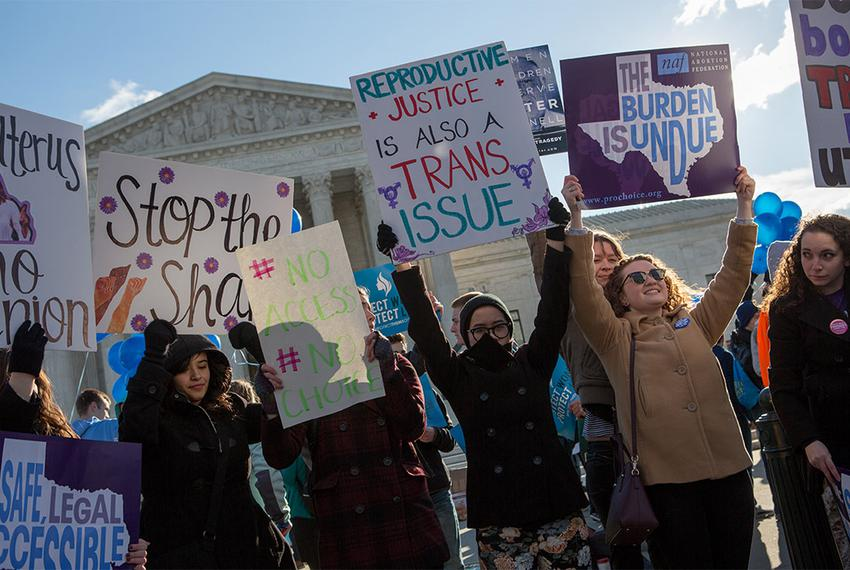 Protesters hold signs in front of the U.S. Supreme Court in Washington, D.C. as Whole Woman's Health v. Hellerstedt is argue…