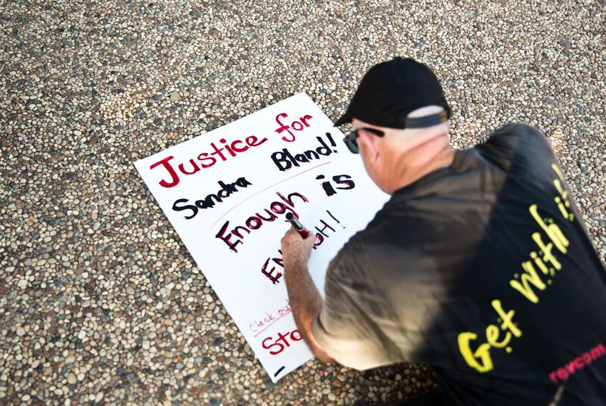 An attendee kneels to makes a sign during the vigil for Bland.