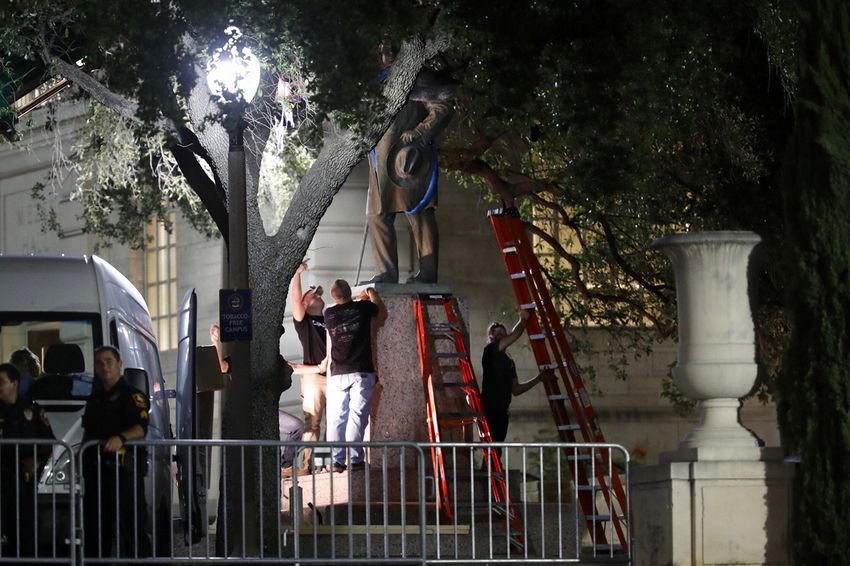 A crew takes down Confederate statues on the UT-Austin campus just after midnight on Monday, Aug. 21, 2017.