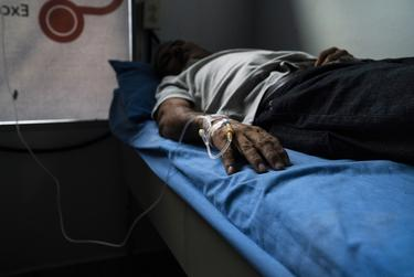 José, Carlos' father, is admitted into a private clinic after health complications. He says he does not work because he falls ill very frequently when he does and earning less than $10 dollars is not enough to afford his medication.