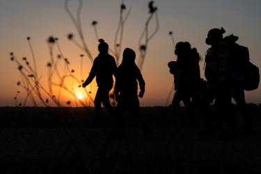 Asylum-seeking migrants' walked towards the border wall after crossing the Rio Grande into the United States from Mexico, in Penitas, Texas on March 26, 2021.