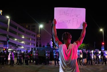 A protester holds a sign in front of a line of Dallas police at a march and rally for George Floyd in Dallas on May 29, 2020.