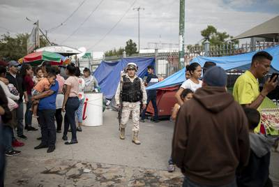 A Mexican soldier patrols a makeshift migrant camp at the base of Paso del Norte International Bridge in Ciudad Juárez. Migrants wait close to the port of entry so they don't lose their spots in line to legally cross into the U.S. and seek asylum.