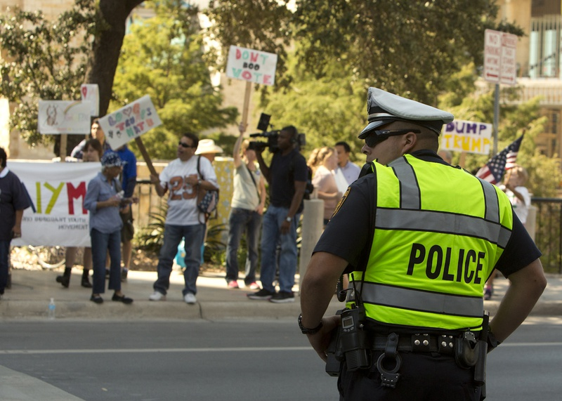 San Antonio police officer in front of group of protesters close to venue where Republican Presidential nominee Donald Trump was attending a fundraiser on October 11, 2016