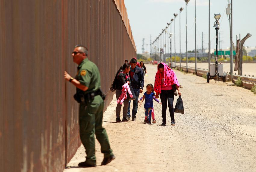 A group of Central American migrants walks next to the U.S.-Mexico border fence after they crossed the borderline while a Bo…