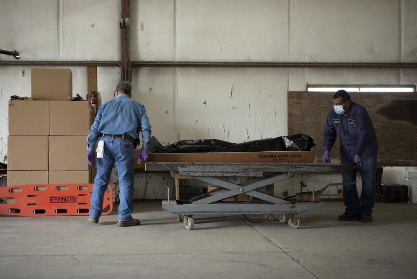 From left, Al Luna and Miguel Guzman move the body of someone that recently died from COVID-19 onto a table. They will short…