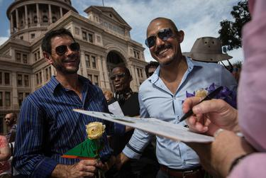 """Herbert Clayson Cloete and Mark Chavez smile as they watch Jodie Flint, who officiated the """"Big Gay Wedding"""" ceremony, sign their marriage license on July 4, 2015 in Austin."""