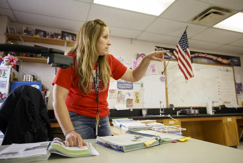 Wendy Stanton, a para-professional whose job includes substituting among other jobs, leads a science class in reading their …