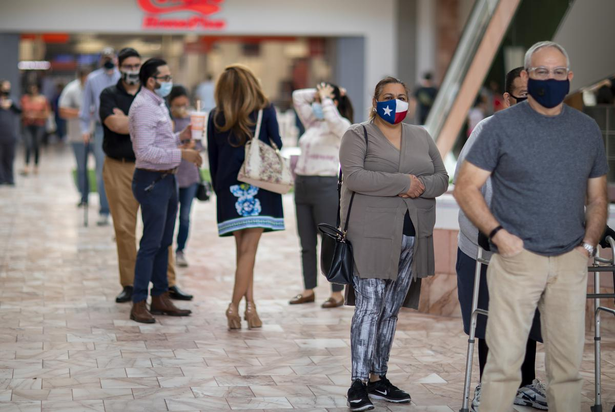 Voters wait in line to cast their ballots on day one of early voting in at the Sunland Park Mall indoor voting site in El Paso on Oct. 13, 2020.