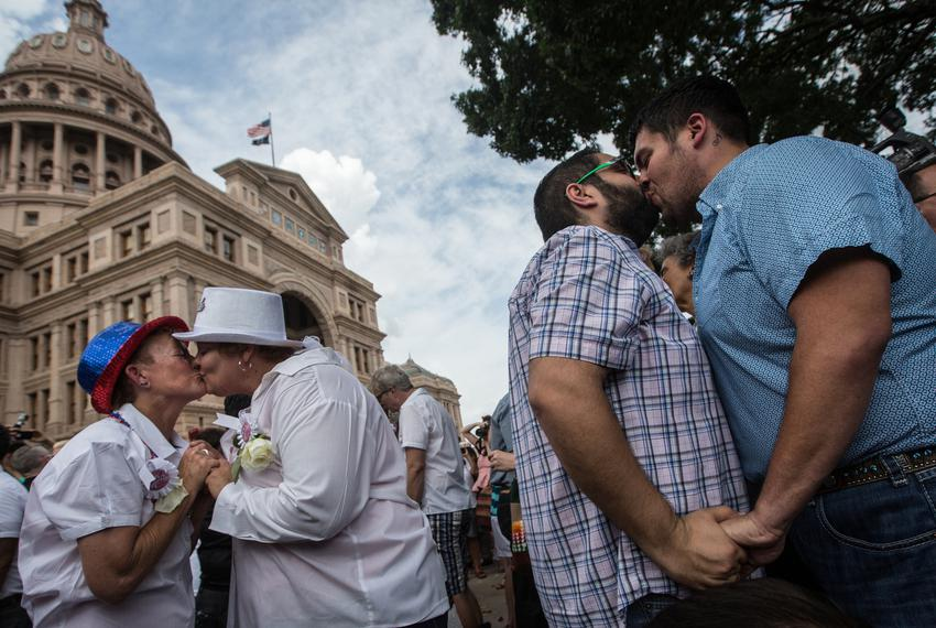 "Couples embrace at the conclusion of the ""Big Gay Wedding"" ceremony on the south lawn of the Texas Capitol on July 4 after..."
