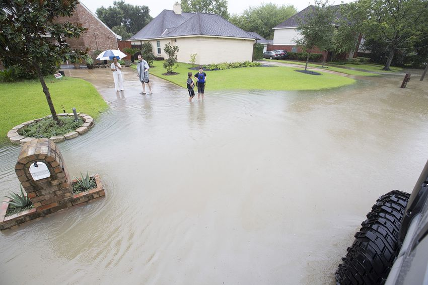 Chris Ginter, center, triesto convince a resident of a flooded neighborhoodnear BuffaloBayou in Houston to evacuate in his monster truck on Tuesday, Aug. 29, 2017.
