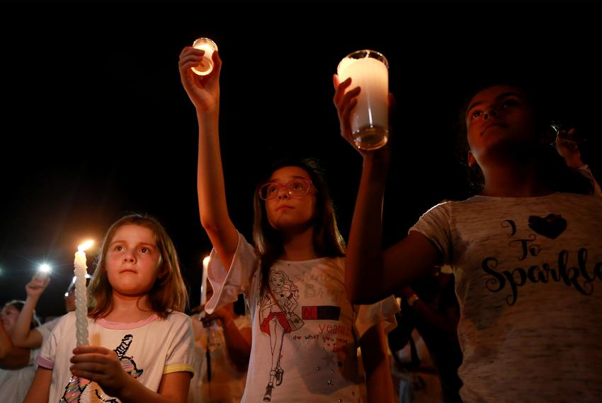 Mourners take part in a vigil near the border fence between Mexico and the U.S after a mass shooting at a WalMart store in...