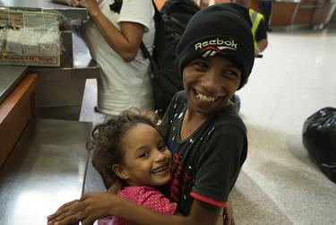 Jose and his sister, Genesis, smile and play at the McAllen Central Station. The family waited for days on the Gateway International Bridge in Brownsville to apply for asylum. They were at the station to get bus tickets.