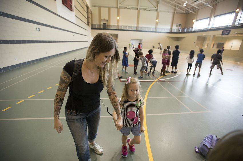 University of Houston student Heather Williams, who is studying marketing, picks up her two kids, including Clover, 5, from a daycare set up by the university after Hurricane Harvey on September 5, 2017.