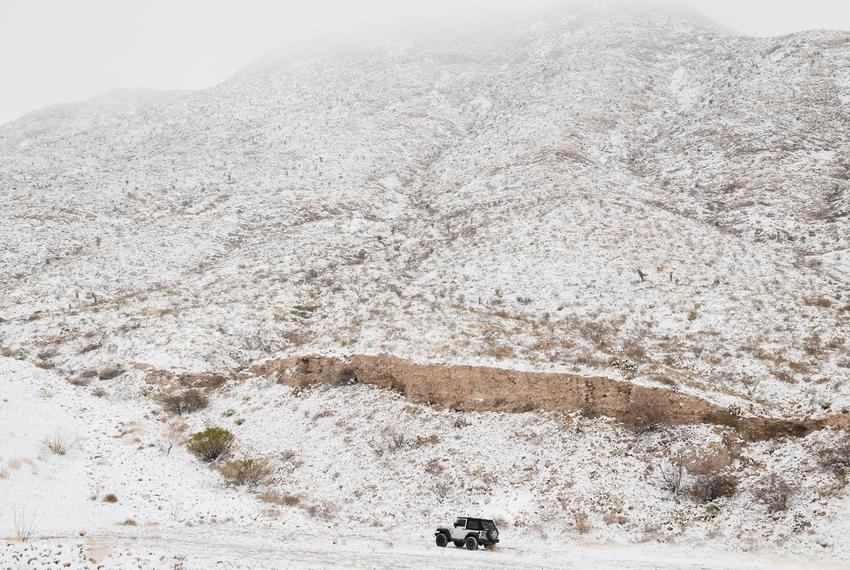 A Jeep drives offroad beneath the snow covered Franklin Mountains in El Paso on Feb. 15, 2021.