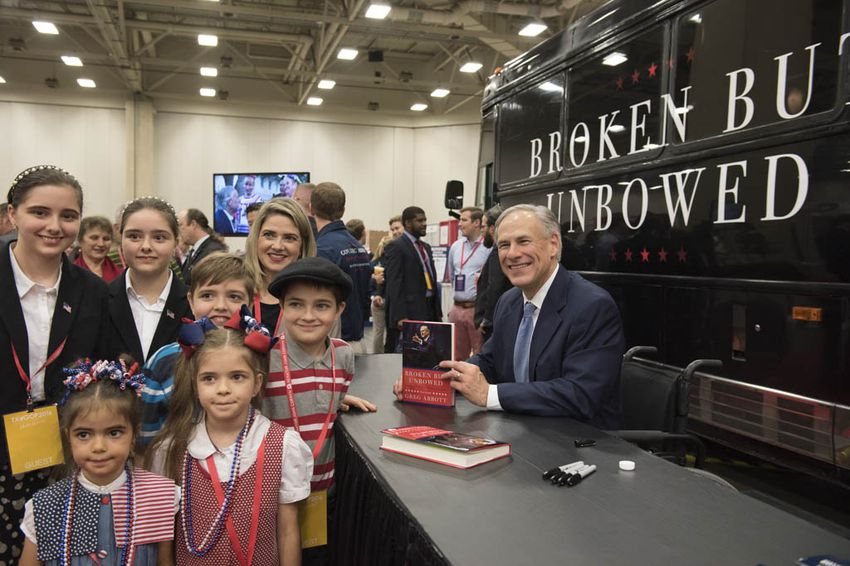 Gov. Greg Abbott poses with the Nelson family from Bedford, TX after signing their book at the trade show of the Republican Party of Texas convention on May 12, 2016.