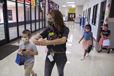 """Kindergarten teacher Mrs. Hogan instructs students to make a """"bubble"""" of room between other students on the first day of in-person classes at Highland Village Elementary on Sept. 8, 2020."""