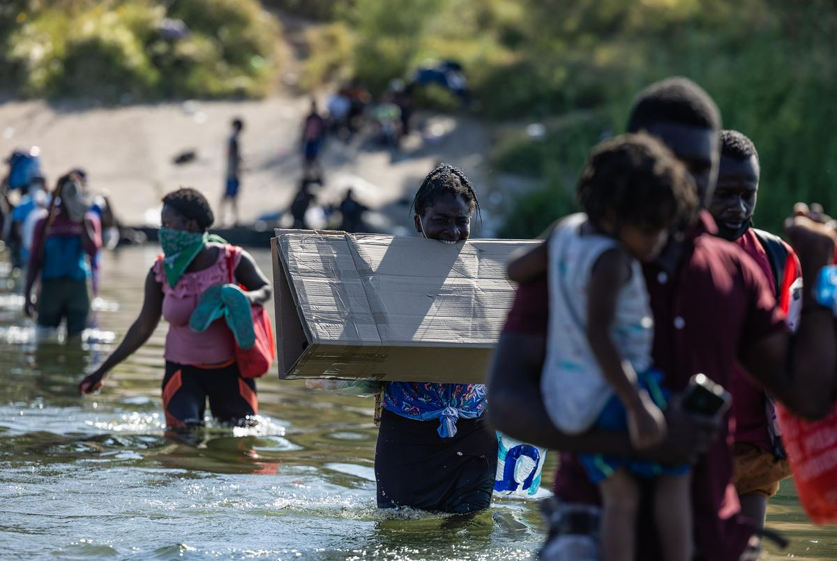 Migrants cross the Rio Grande with food, water, shelter, clothing, and other supplies as they prepare to spend the night under the International Bridge in Del Rio on Sept. 16, 2021.