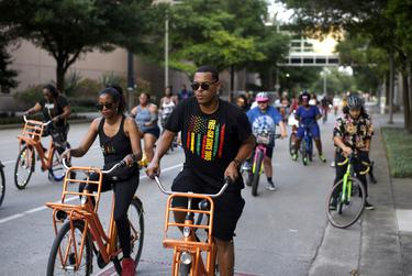 Lawrence Taylor, center, rides his bike during a Juneteenth celebration bike ride in Houston on June 18, 2021.