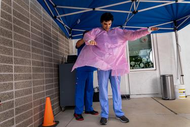 Dr Gandi, with the help of his medical assistant, begins to put on personal protective equipment at his drive-thru testing facility in northeast Austin on June 1, 2020.