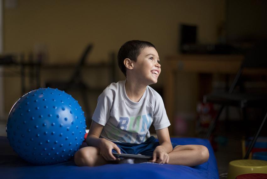 Octavio Armendariz, 8, smiles as he watches cartoons on his iPad in his living room at his home in El Paso, Texas. Octavio h…