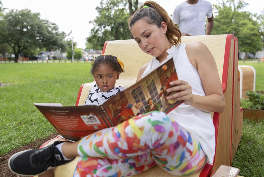 Alejandrina Flores Reyna reads to her daughter Sira during the unveiling of Violette Bule's public art installation 'Rethink…