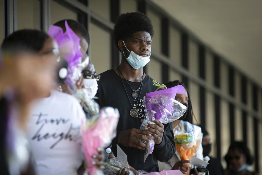 A man holds a bouquet of flowers at the Fountainlife Center as he waits in line to board a shuttle to the memorial for Georg…