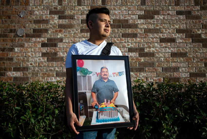 Cristobal Onofre holds a framed photo of his father from his 44th birthday party in Houston. Onofre lost his father to COV...