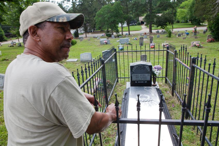 Reverend Rodney Norsworthy, a minister at Mount Olive Missionary Baptist Church, shows the grave of James Byrd, at a cemet...