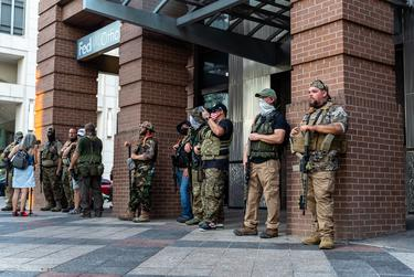 Members of the far-right Proud Boys militia stand on Congress Avenue across from the Garrett Foster memorial in downtown Austin.