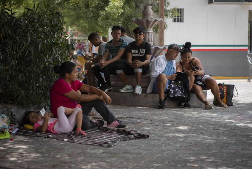 A group of migrants wait at a small plaza near the Gateway International Bridge in Matamoros, Tamualipas. The group is waiting to ask for asylum in the United States.