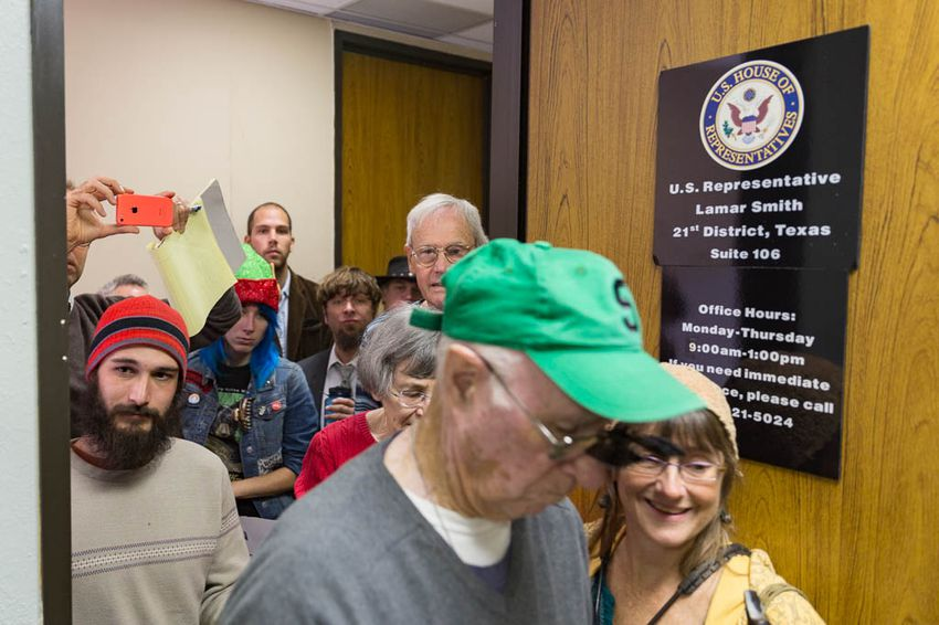 """Climate change activists crowd Representative Lamar Smith's office to present him with the """"Flat Earth Foundation of Texas"""" Award for """"Semi Skeptic"""" of Distinction on Dec. 7th, 2015. Photo by: Shelby Knowles"""