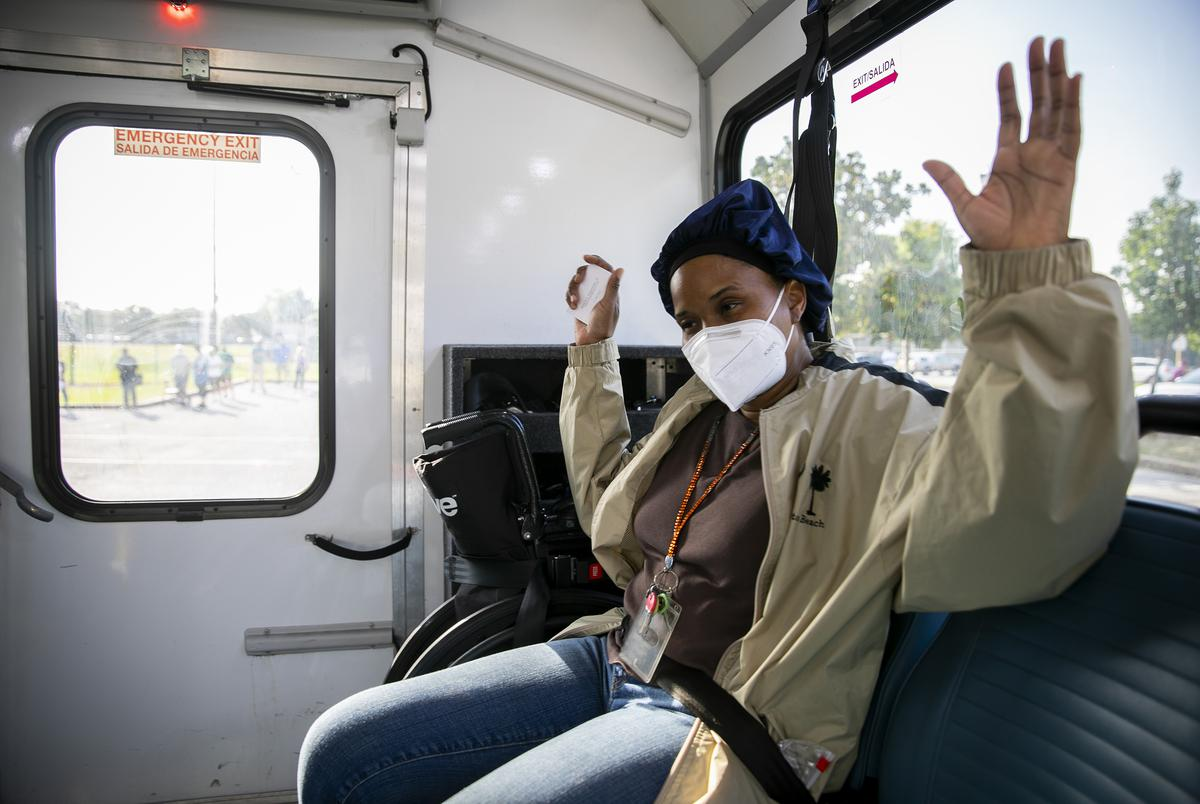 Voter Lovely Washington cheers aboard a METROLift vehicle after casting her ballot during the first day of early voting in Houston on Tuesday, Oct. 13, 2020. Washington hopes to her vote is used to improve things in America.
