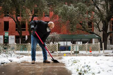 Executive director and Vice President of DMA Properties Sergio Amaya clears the walkways outside of the Rebekah Baines Johnson Center on Feb. 17, 2021.