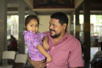 Walter Sanchez Reyes holds his daughter Maria Dolores Sanchez at a migrant shelter in southern Mexico. Sanchez was shot by gang members while driving a bus in Tegucigalpa, Honduras. The family plans to request asylum in the United States.