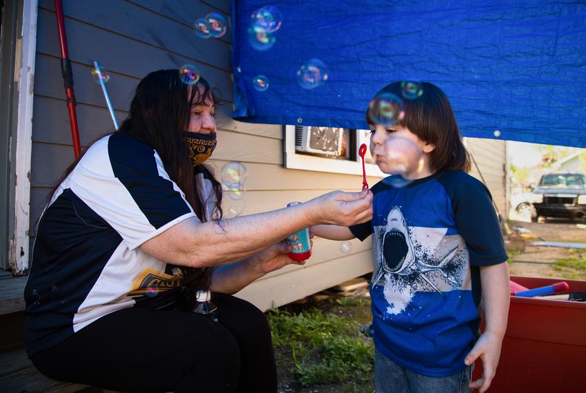 Lucille Hammash helps her grandson, Noah Proctor, blow bubbles in the sideyard of their home in central Houston, on April 11…
