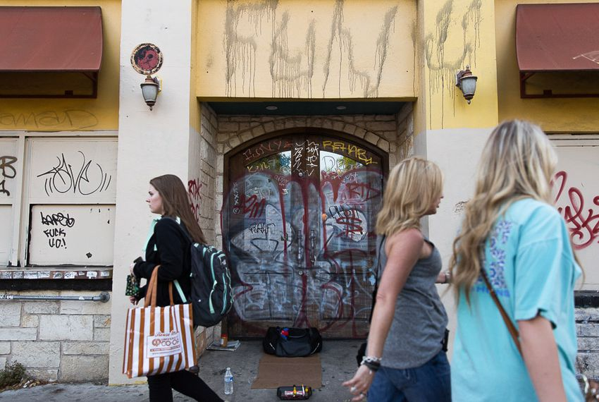 Students walk past a heavily graffitied building that once was Mellow Mushroom on Guadalupe Street next to the University of Texas campus on April 9, 2016.