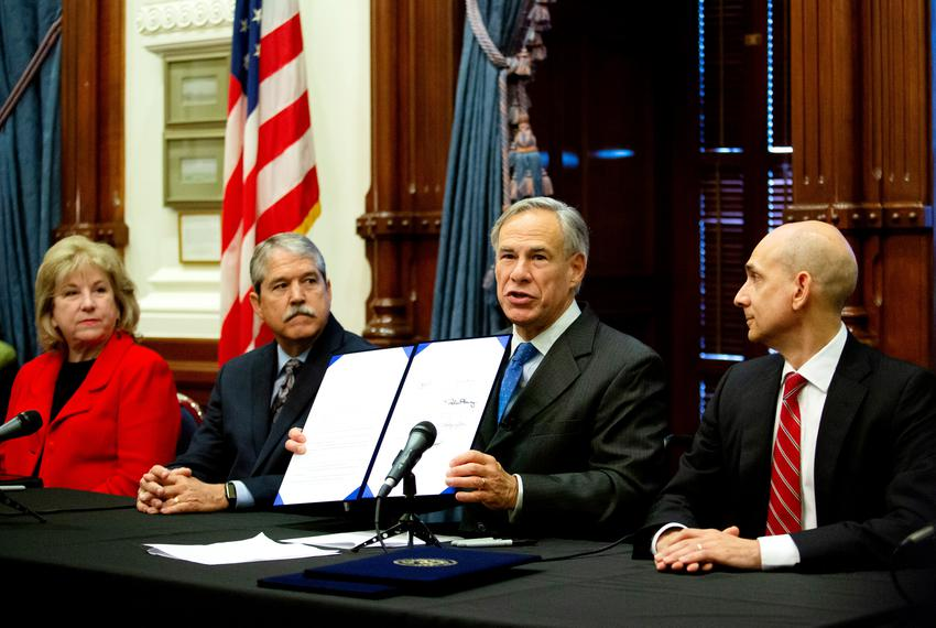 From left: State Sens. Jane Nelson, Larry Taylor and state Rep. Greg Bonnen look on as Gov. Greg Abbott talks about bills he…
