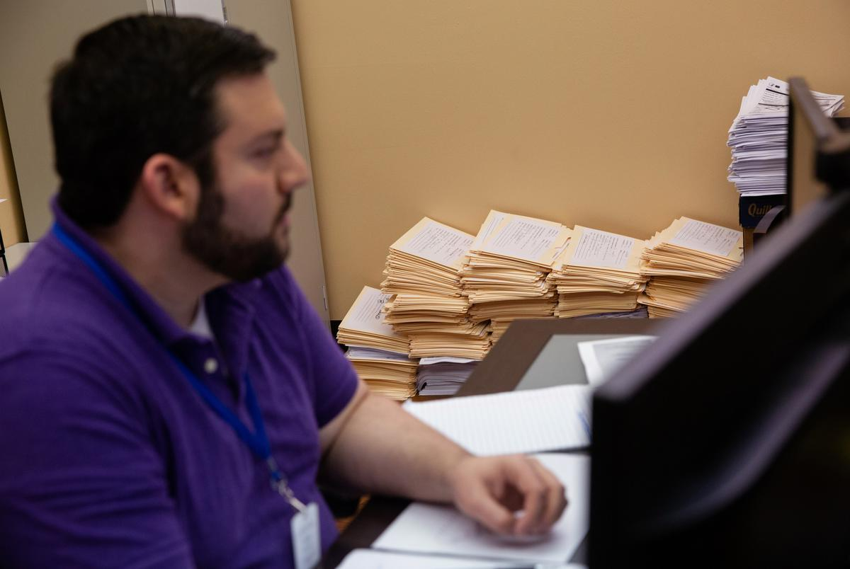 Epidemiologist Jason Geslois works at his desk at the Northeast Texas Public Health office in Tyler on Sep 22, 2020. Stacks of folders contain records and information of COVID-19 cases across seven counties in northeast Texas.