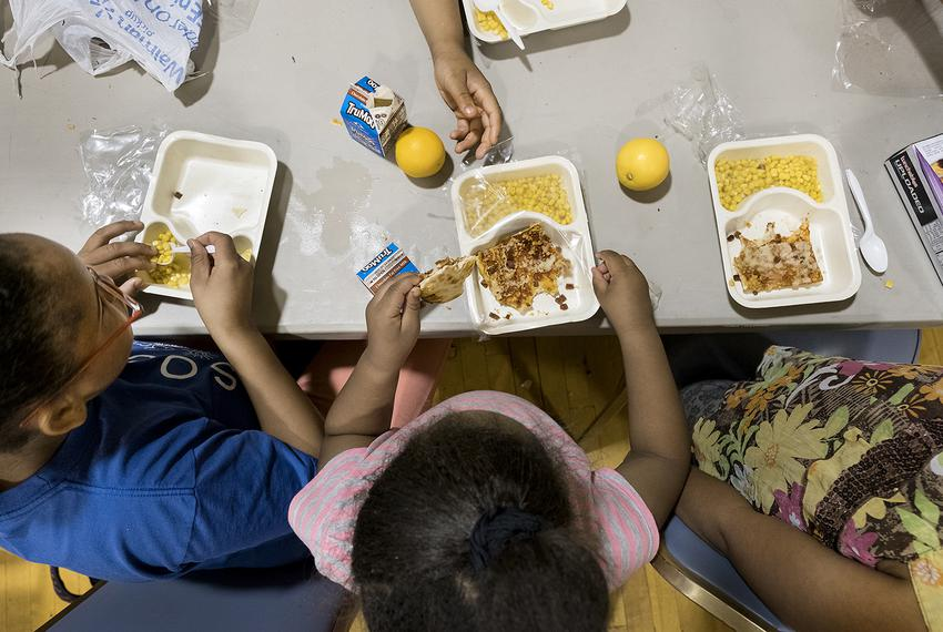 Siblings Stacy Hurd, 11, Angelica Hurd, 5, and Sheniya Hurd, 8, eat a free meal together at Jarvis Christian College in Hawk…
