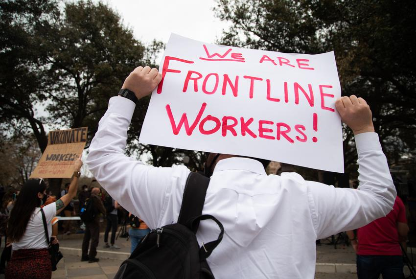Protestors hold signs advocating for the protection of frontline workers at the Capitol on March 8, 2021.  The rally is in r…