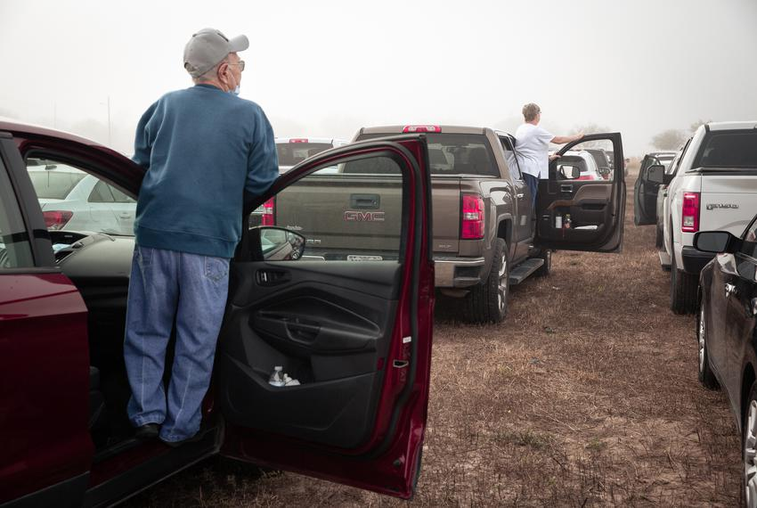 Eager valley residents look amongst the rows of cars lined up at the Rio Grande Valley Livestock Show Grounds in Mercedes. A…