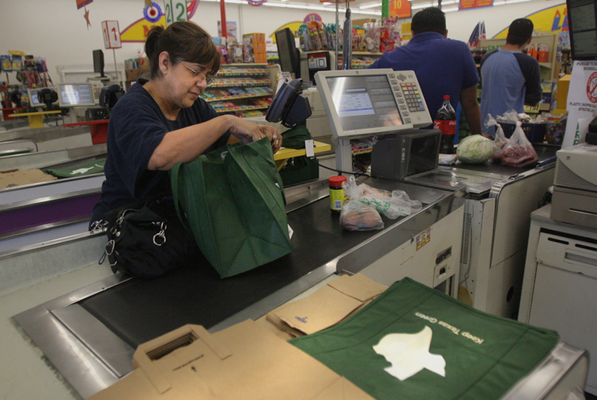 Brownsville resident Rosie Orozco bags her own groceries in a reusable bag after shopping at an A.V. Lopez grocery store. ...