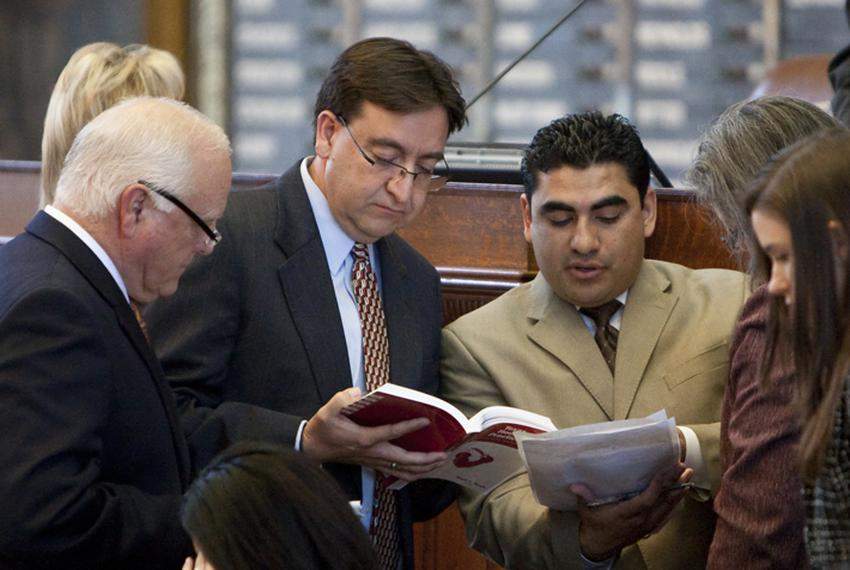 Rep. Peter Gallego D-Alpine reviews the Texas House Practice book with Rep. Armando Walle D-Houston while discussing HB 14 r…