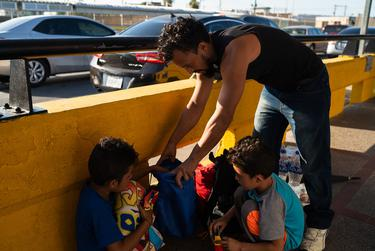 José, 35 and his sons Dariel, 10 and Ezequiel, 7, from Honduras, get ready to be processed after waiting to seek asylum on the Mexico side of the Gateway International Bridge in Brownsville, Texas, for three days.